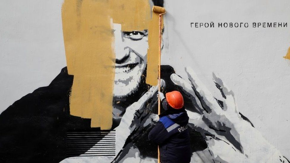 A worker paints over a graffiti depicting jailed Russian opposition politician Alexei Navalny in Saint Petersburg
