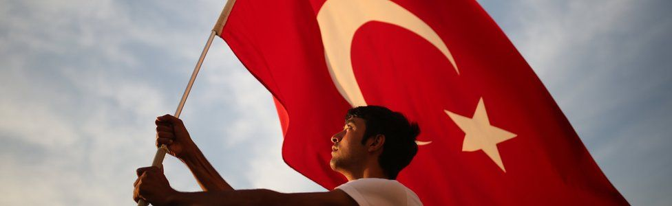 A man waves a national flag as thousands of people march to protest against the deadly attacks on Turkish troops, in Izmir, Turkey on 9 September, 2015