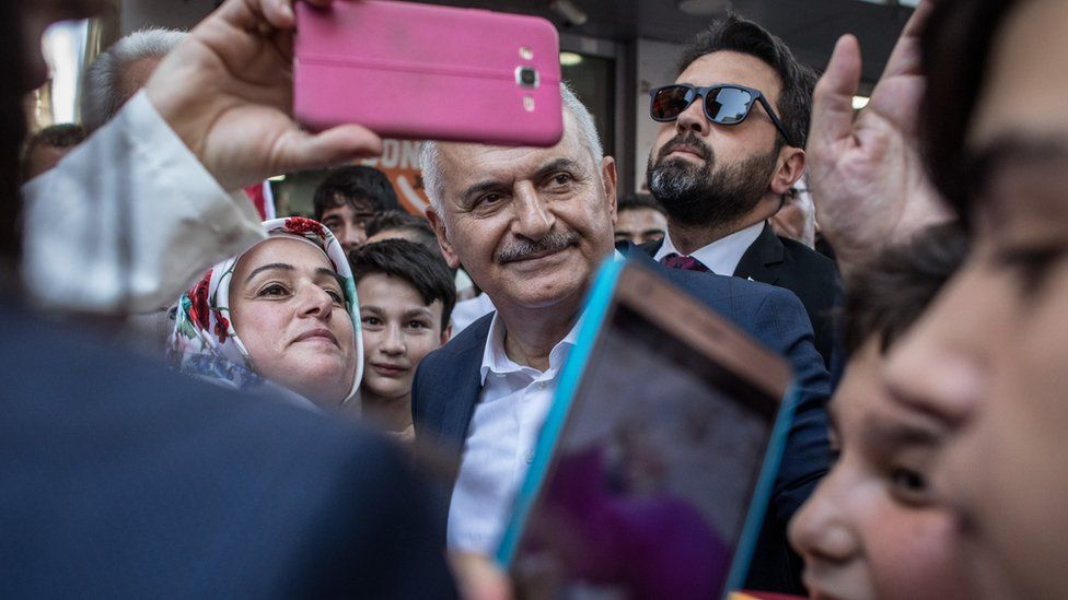 Binali Yildirim of the ruling Justice and Development Party (AKP) meets with supporters during a campaign street stop on June 18, 2019 in Istanbul