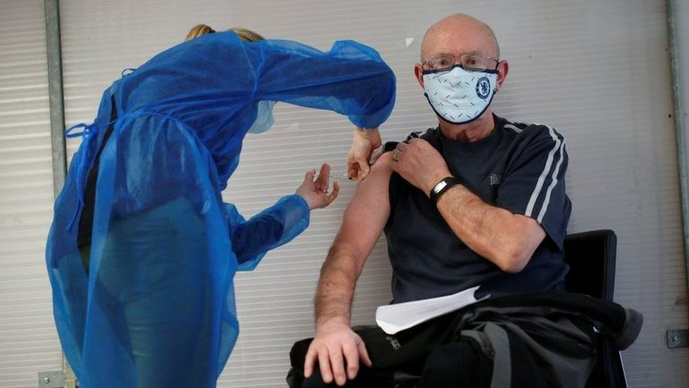 An elderly man, over 75 years of age, receives a dose of the Pfizer-BioNTech COVID-19 vaccine