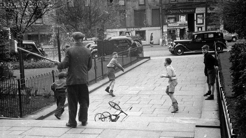 A man with a broom chases away a group of unruly boys from a Dundee park