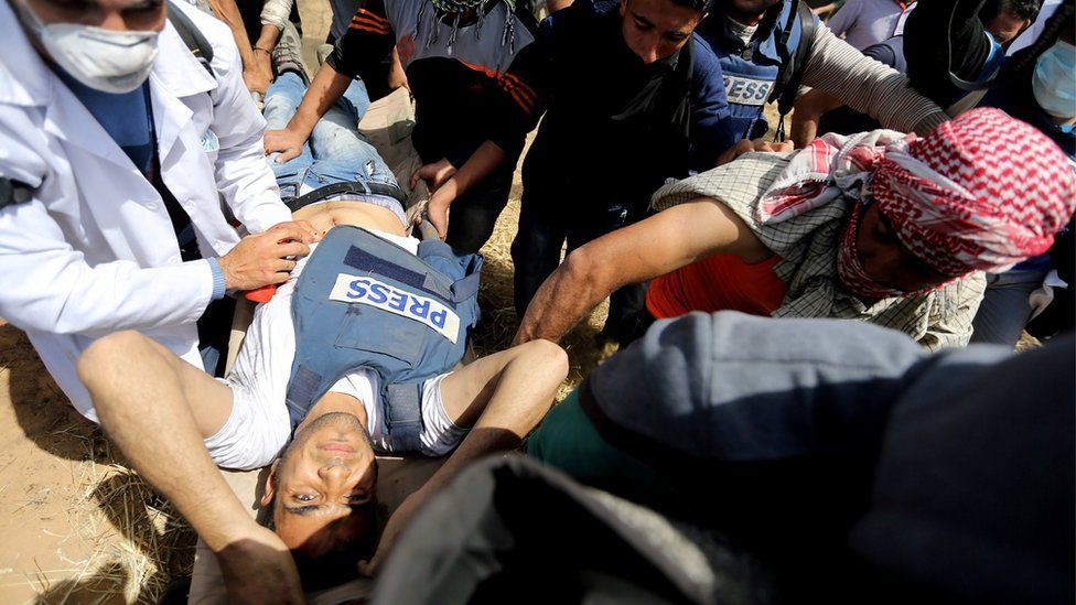 Mortally wounded Palestinian journalist Yasser Murtaja, 31, is evacuated during clashes with Israeli troops at the Israel-Gaza border