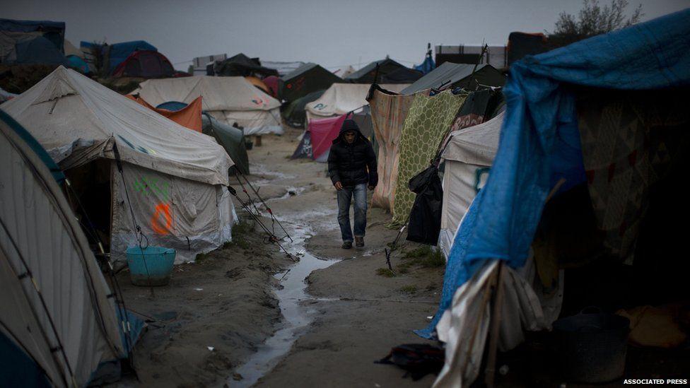 A man walking between tents