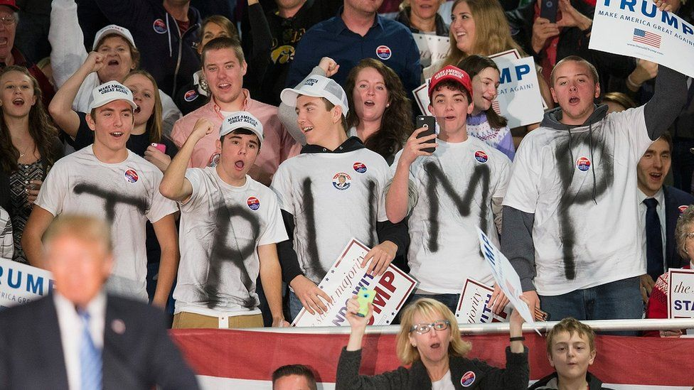 """Supporters wear t-shirts spelling out """"Trump"""" at an iowa rally."""