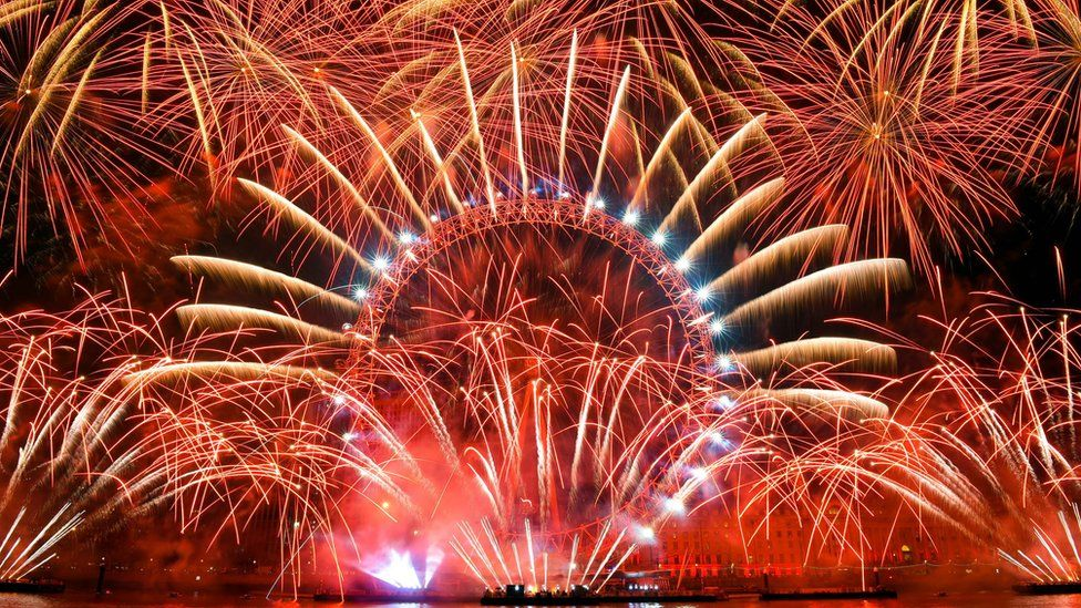 Fireworks explode over the iconic London Eye marking the beginning of the New Year in central London