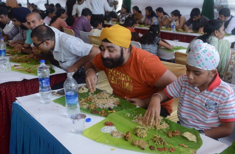 Indian diners eat a special mass lunch of 27 vegetables curries known as 'Onam Sadya' in New Delhi on September 17, 2013