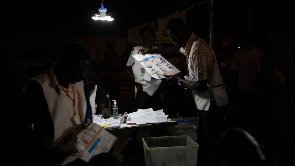 An electoral commission official holds a ballot paper during vote counting at a polling station during Burkina Faso's presidential and legislative elections, on November 22, 2020 in Ouagadougou.