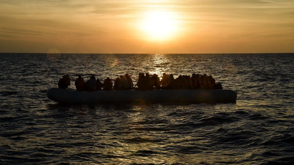Migrants and refugees sit on a rubber boat in a boat off the coast of Libya - 5 November 2016