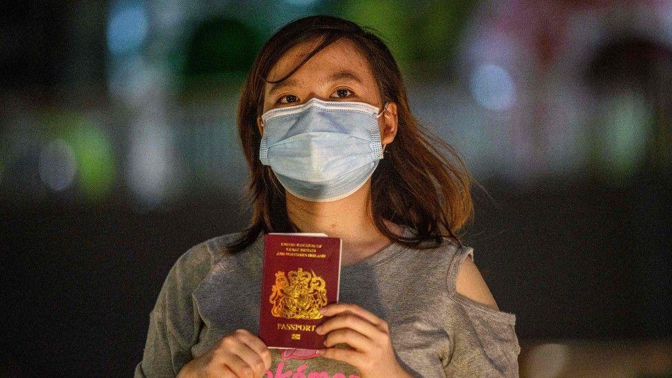Mujer con mascarilla y pasaporte.