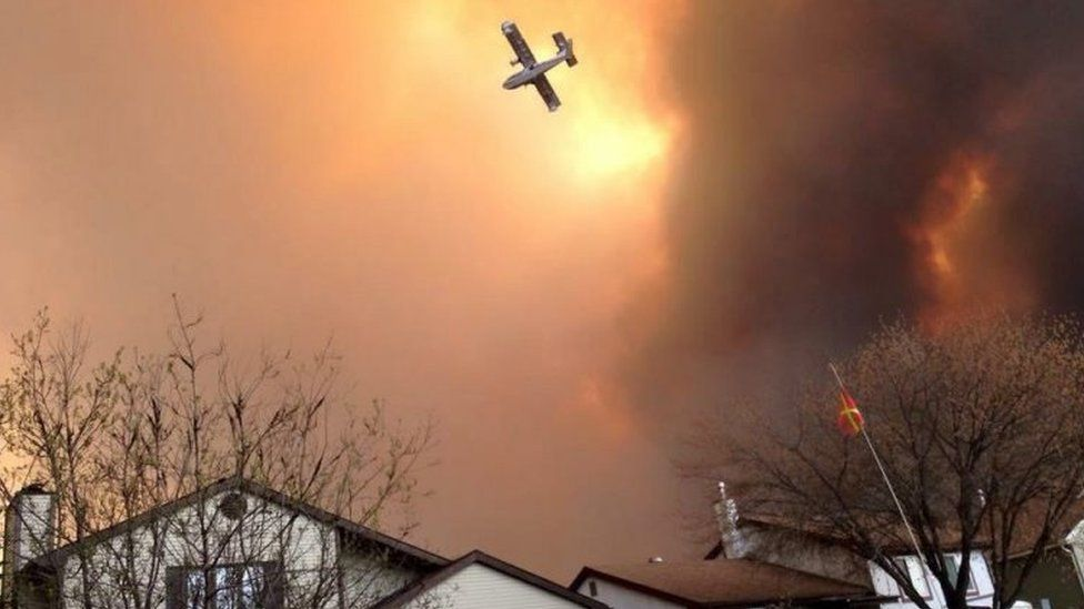 Smoke fills the air as a plane flies over Fort McMurray