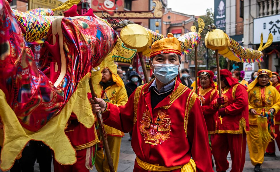 Performers in Wuhan, central Hubei province, wear face masks as they prepare for the traditional dragon dance. Photo: 26 February 2021