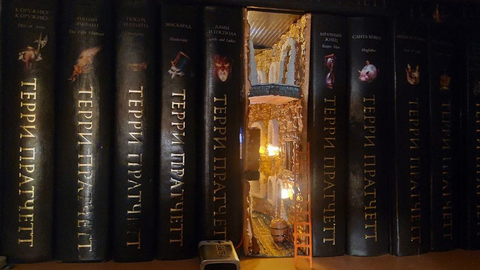"""A """"book nook"""" - a small diorama of an alleyway visible between books on a bookshelf"""