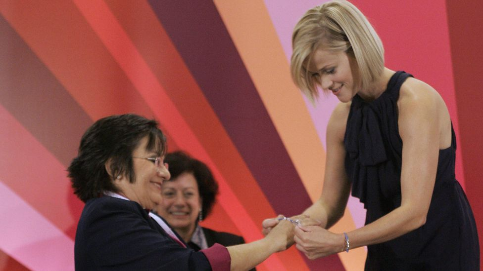 US actress Reese Witherspoon (R) puts a campaign bracelet on biochemist and domestic violence survivor Brazilian Maria da Penha (L) during an event to spread a message of female empowerment, in Sao Paulo, Brazil, on August 28, 2008.