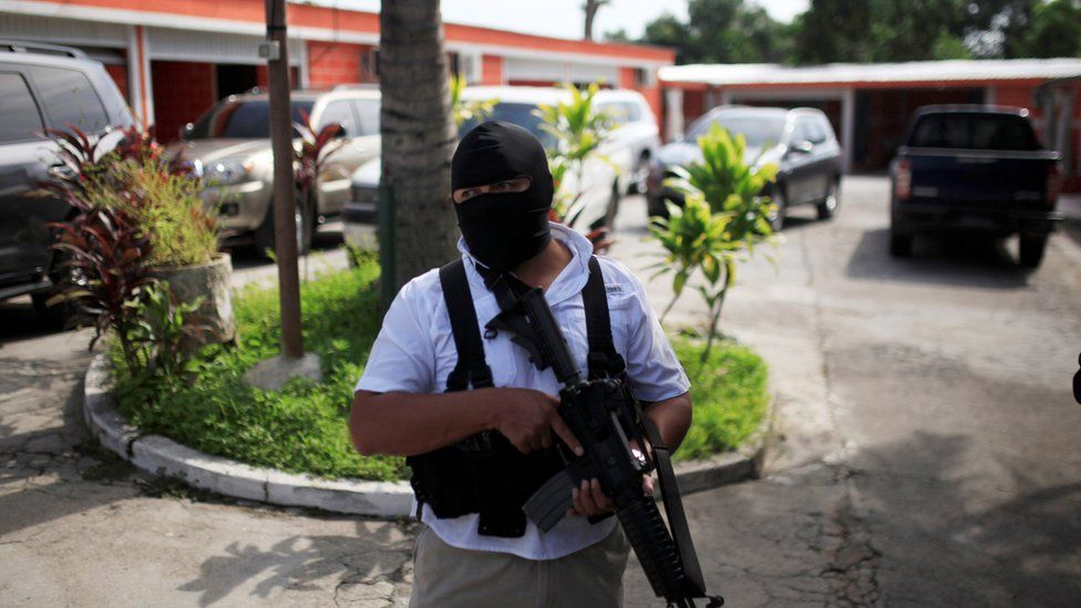 A policeman stands guard outside a motel seized in a raid in El Salvador