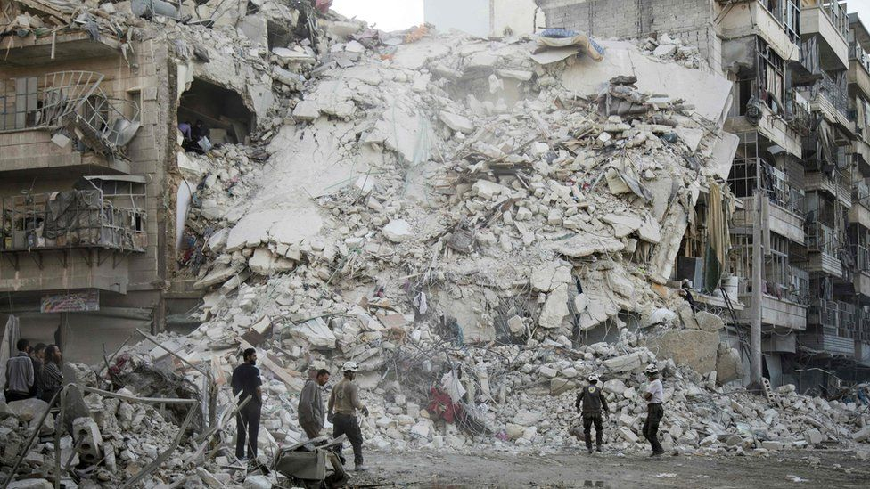 Rescue workers search for victims amid rubble of a destroyed building following reported air strikes in the rebel-held Qatarji district of Aleppo (17 October 2016)