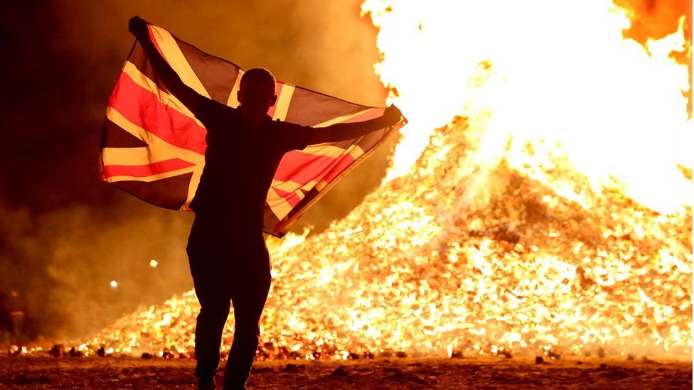 Bonfire lit with man holding union flag