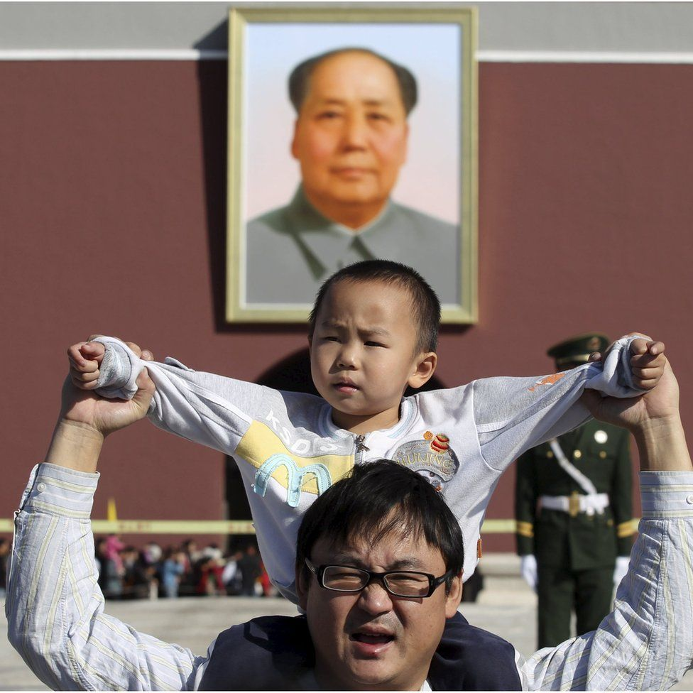 A boy sits on his father's shoulders as they pose for a photograph in front of the giant portrait of late Chinese chairman Mao Zedong on the Tiananmen Gate, in Beijing, China, October 2011.