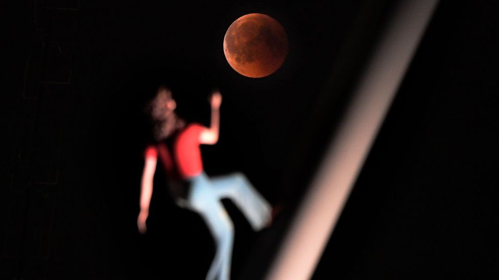 A 'blood moon' eclipse is pictured with a sculpture by the American artist Jonathan Borofsky 'Woman walking to the sky' on July 27, 2018 in Strasbourg, eastern France.