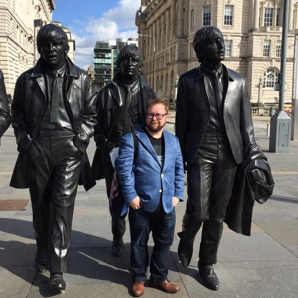 Allan in front of a statue of the Beatles