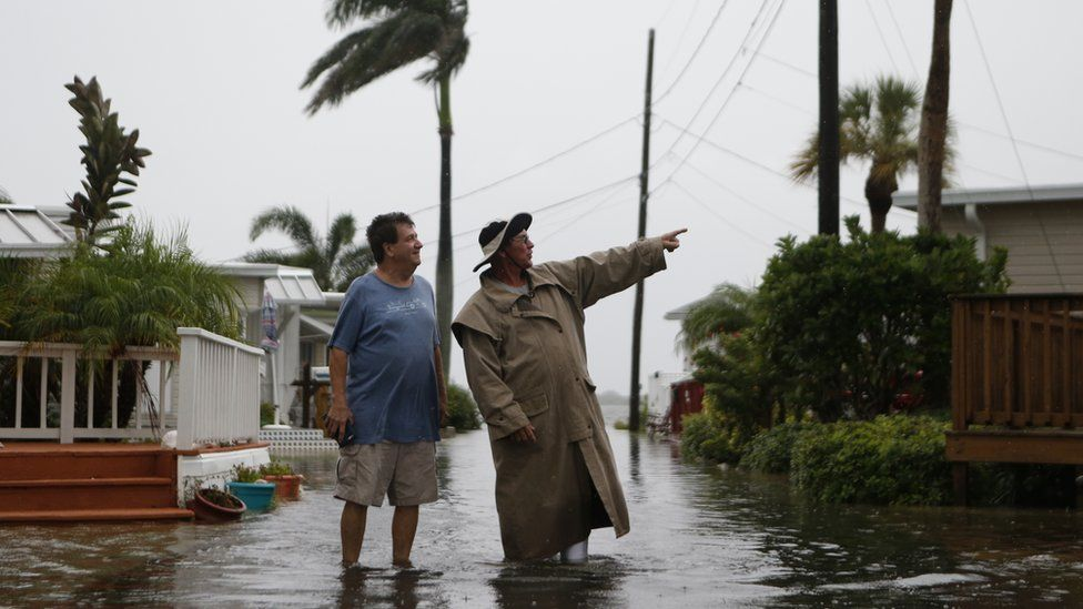 Residents of the Sandpiper Resort survey the rising water coming from the Gulf of Mexico into their neighbourhood as winds and storm surge associated with Tropical Storm Hermine impact the area on 1 September 2016 at in Holmes Beach, Florida.