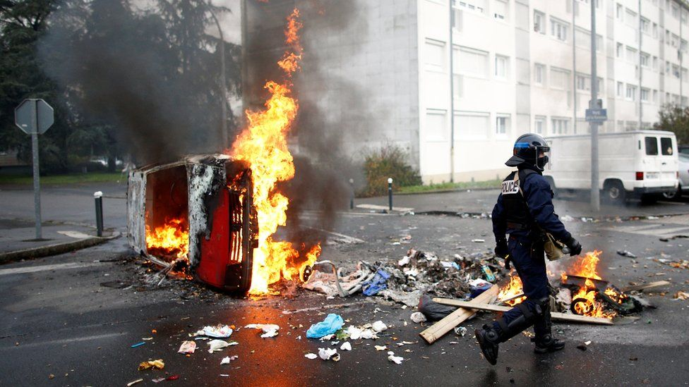 A French riot policeman walks past a burning car as youth and high school students protest against the French government's reform plan, in Nantes, France, December 6, 2018