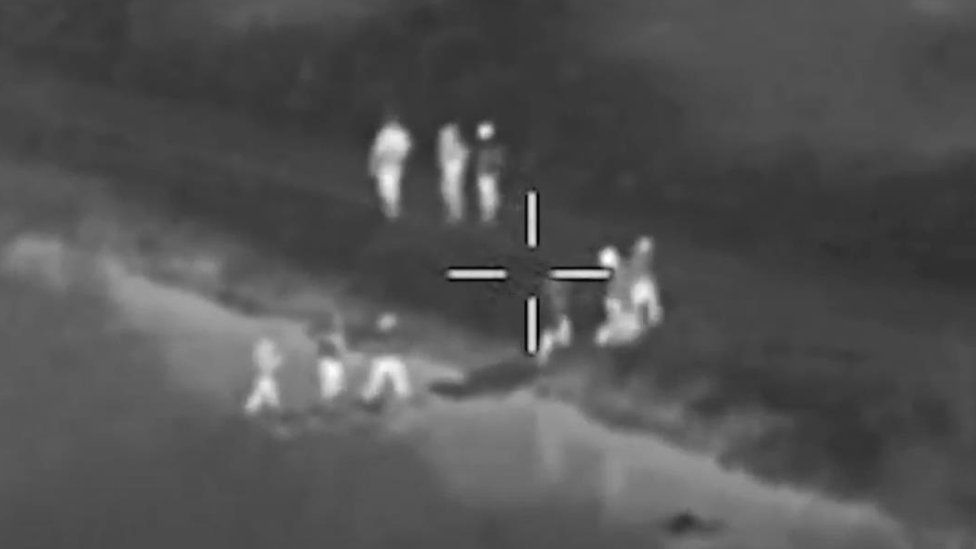 Footage shows people crossing a river to leave the scene