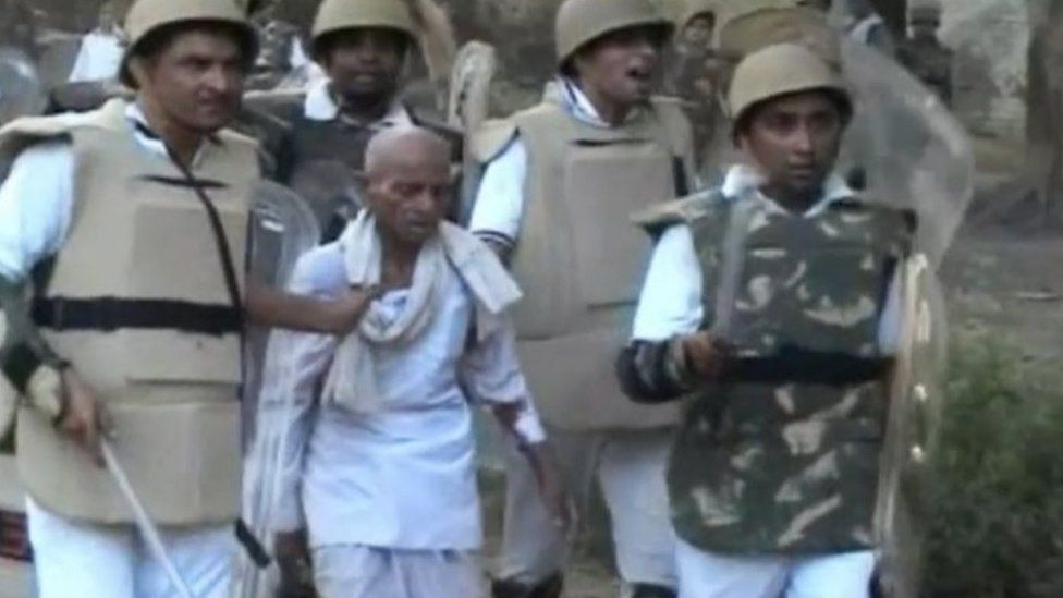 In this Thursday, June 2, 2016 image made from video, paramilitary soldiers detain an unidentified man from the site of violent clashes in Mathura, India