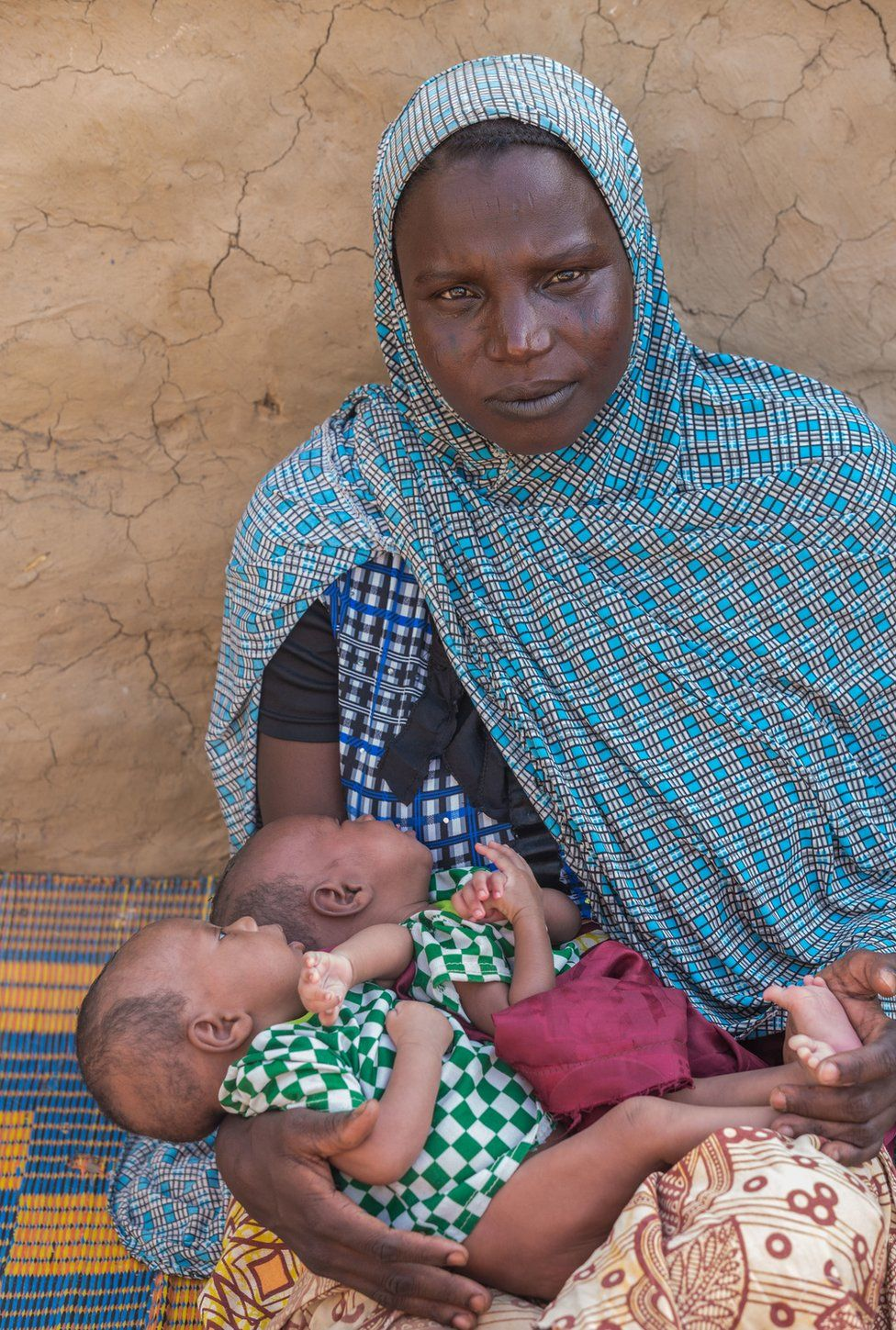 Soumaila Soumana's wife holds two-month-old twins Hassana and Housseina outside their home in Norandé