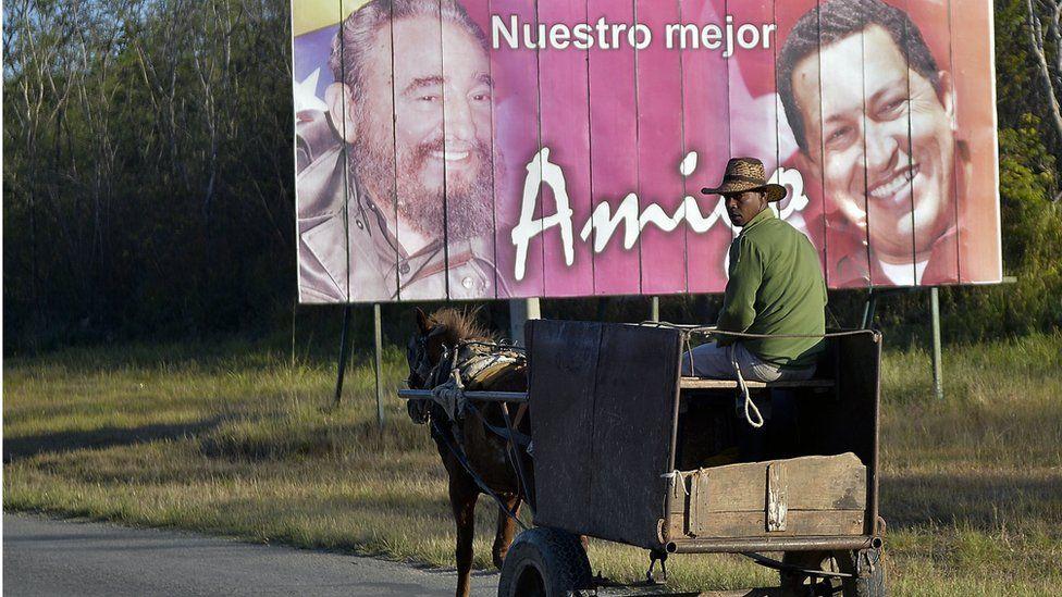 A man rides a horse-drawn cart near a poster