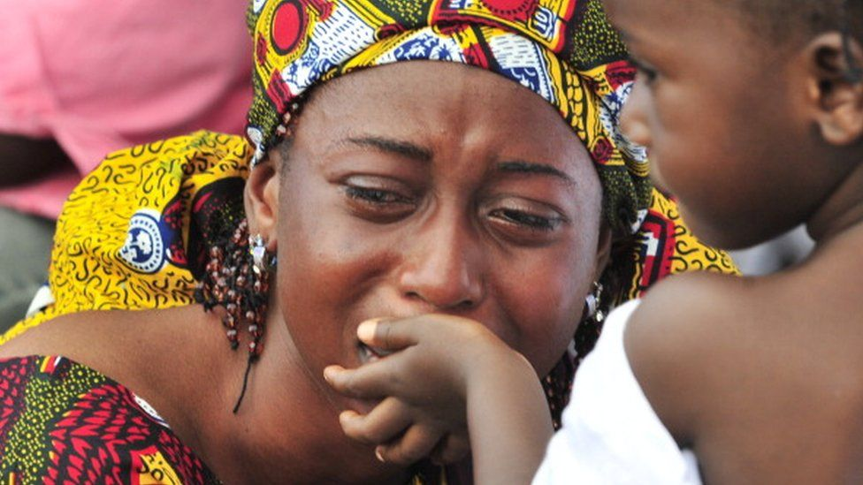 A young girl tries to comfort her mother during a burial ceremony for victims of the post-election violence at the municipal cemetery of Abobo in Abidjan on October 13, 2011