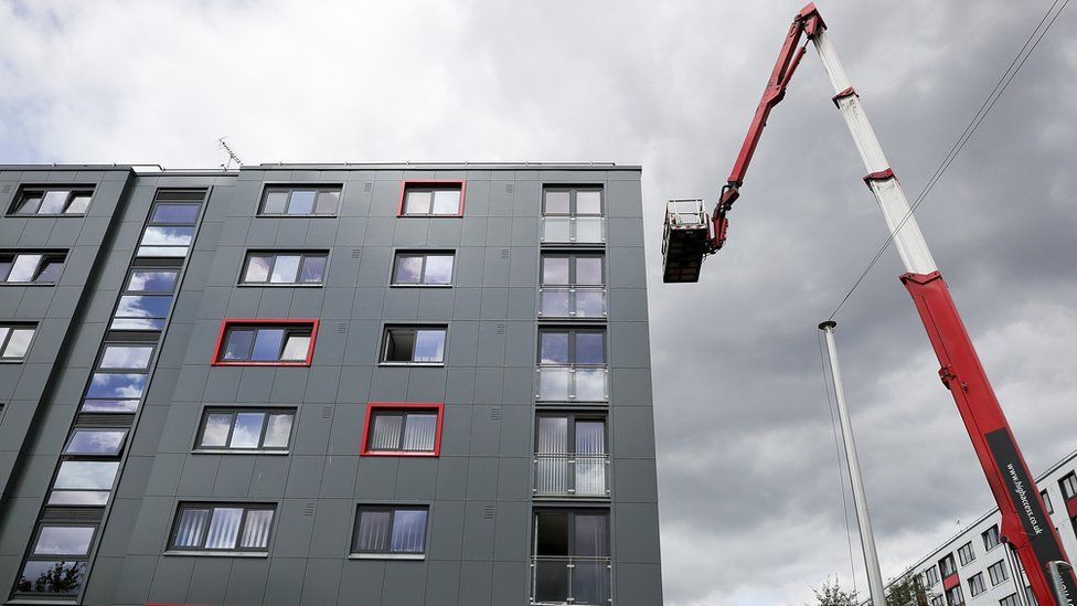 Cladding tiles being removed from a block in Salford for testing