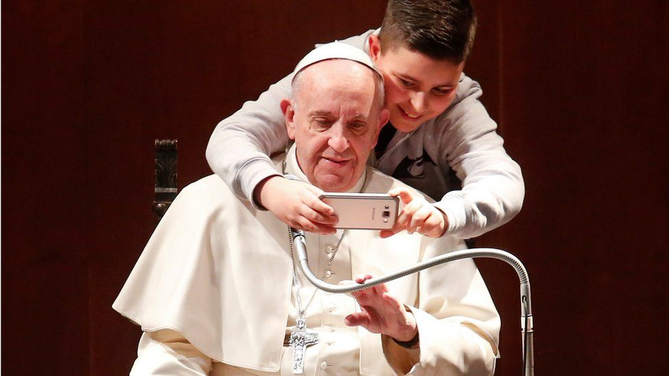 A boy takes selfies with Pope Francis during a visit at the parish of St. Mary Josefa of the Heart of Jesus in Rome