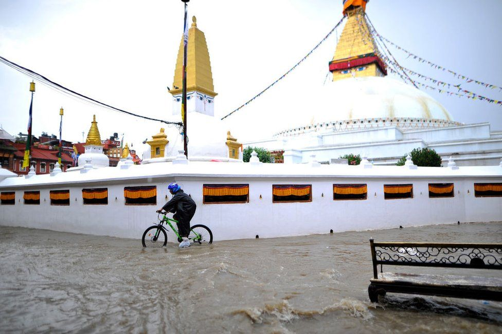 A cyclist travelling in a flooded water in the premises of Boudhanath Stupa, a UNESCO World Heritage Site in Kathmandu, Nepal on Thursday, September 06, 2018.