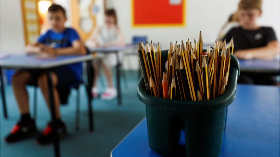 A pot of pencils in a classroom, with children sitting at desks in the background