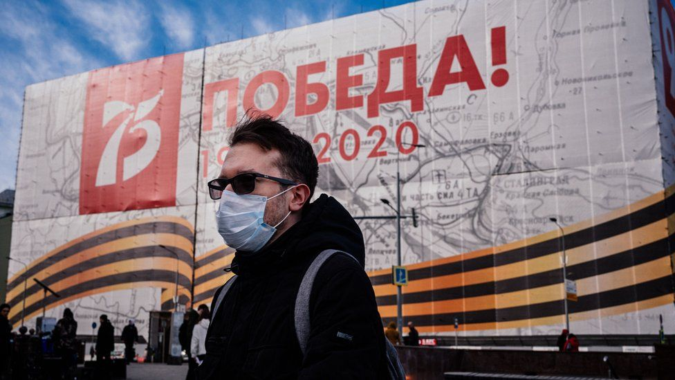 A man wearing a face mask, amid concerns of the COVID-19 coronavirus, walks in front of a huge banner for the upcoming 75th anniversary of the victory over Nazi Germany in World War II