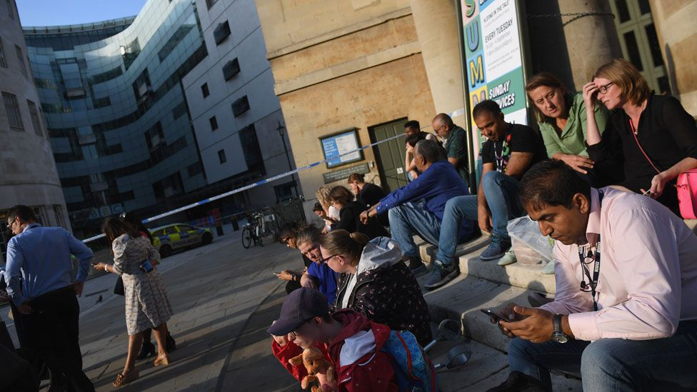 People sat outside the cordon put up outside the BBC