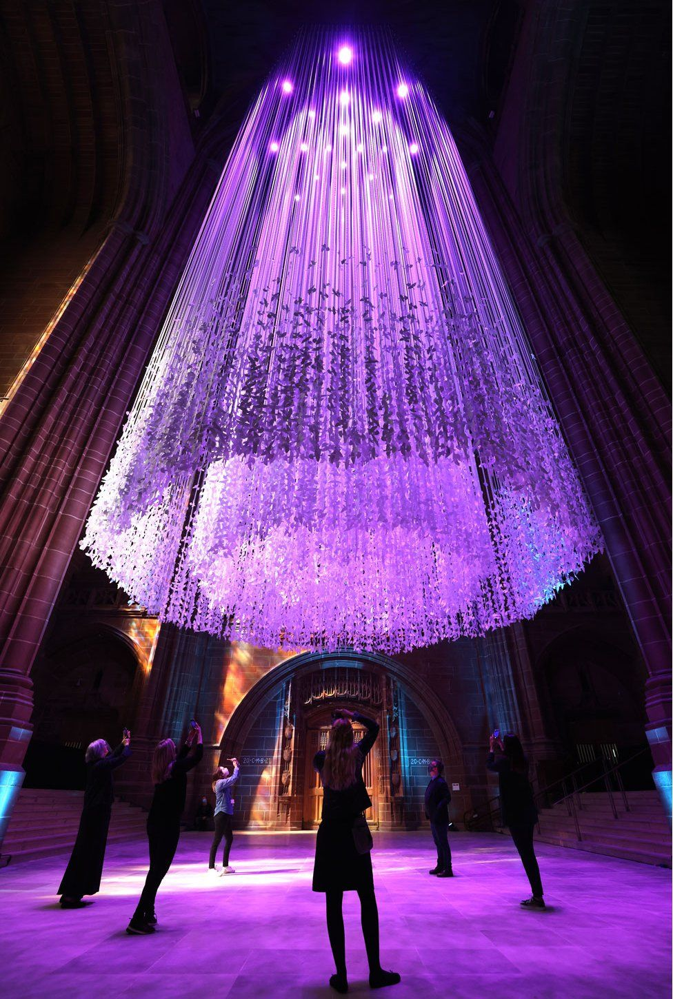 Visitors look at thousands of paper doves suspended from the roof of Liverpool Cathedral