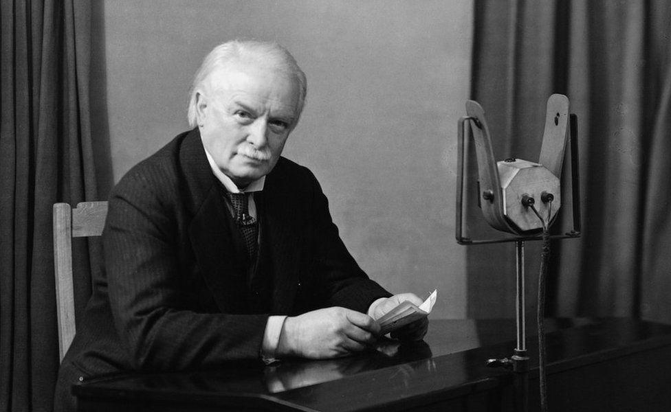 David Lloyd George sitting at a microphone