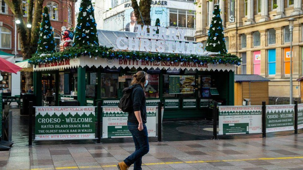 A man passes a festively decorated Hayes Island Snack Bar in Cardiff city centre