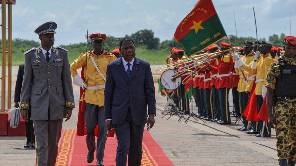 Burkina Faso coup leader General Gilbert Diendere (left) walks with the President of Benin Yayi Boni (third from left) shortly after his arrival at the airport in the capital Ouagadougou, Burkina Faso,