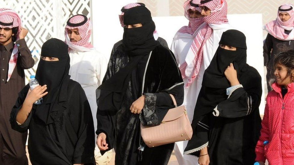 Saudi women in abayas and niqabs