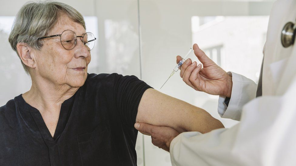 Stock photo of a woman being injected by a doctor