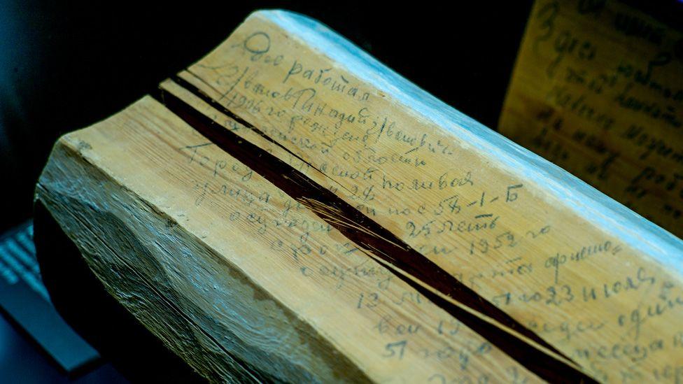 Log with prisoner's message scrawled on it