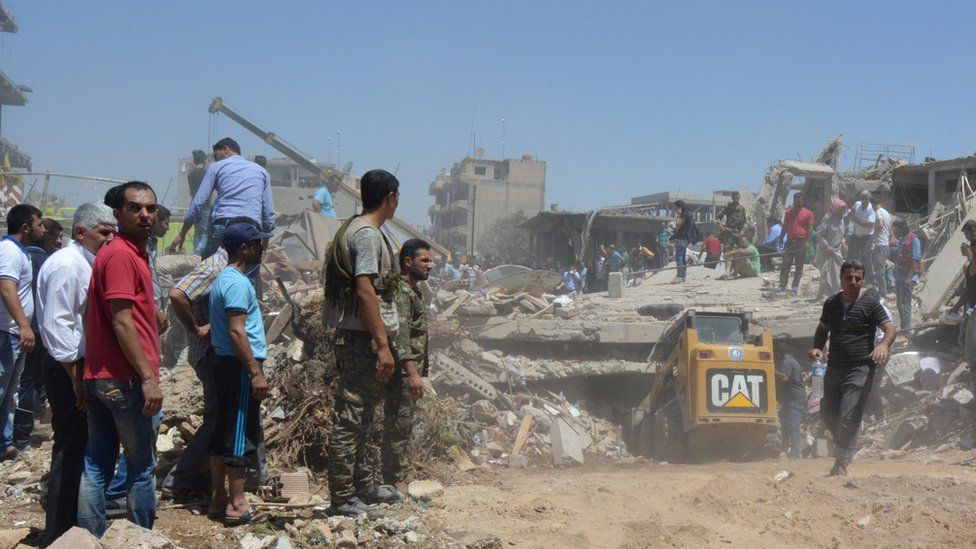 People use a digger and crane to look for survivors under debris at a damaged site in Qamishli (27 July 2016)