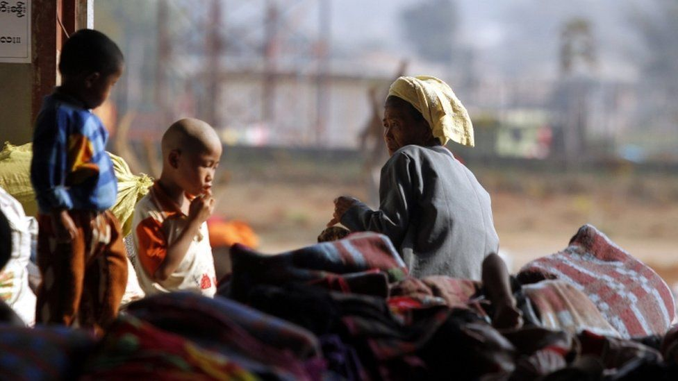 Refugees from northern Myanmar sit on a pile of blankets inside a monastery which has been set up as temporary refugee camp in KyaukMe, northern Shan State, Myanmar, 21 February 2016