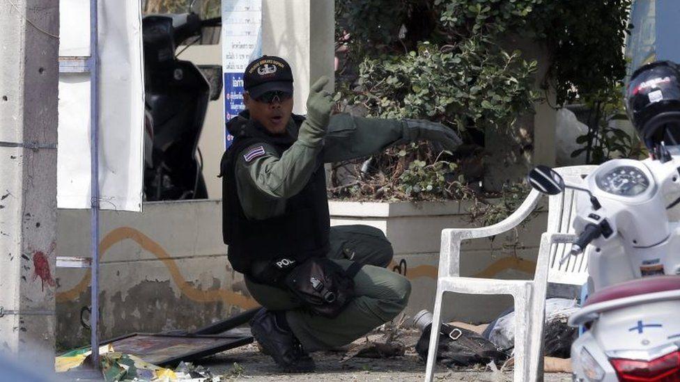 A Thai policeman helps an injured victim following a bomb attack in Hua Hin, Thailand, 12 August 2016.