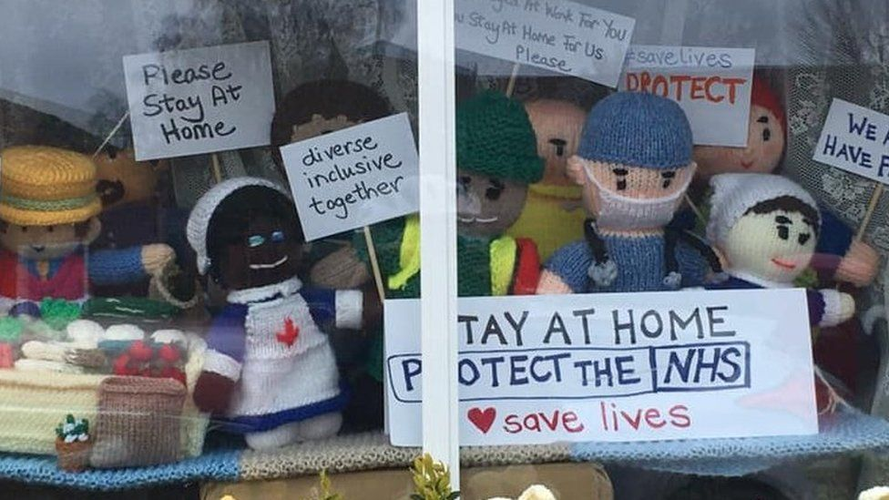 """Knitted figures in window with signs """"Stay at home. Protect the NHS"""" and """"We stayed at work for you now stay at home for us please"""""""