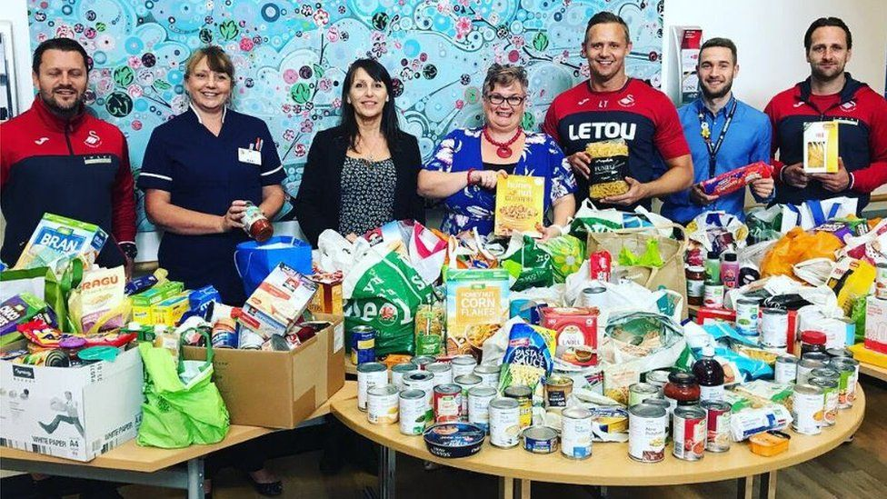 Lee Trundle (third from right) with MP Carolyn Harris (fourth right), Morriston Hospital nurse director Nicola Williams (second left) and members of the Swans Community Trust during the collection from Morriston Hospital