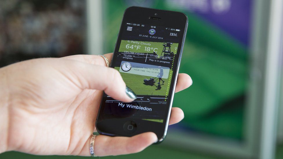 Woman holding smartphone showing tennis app