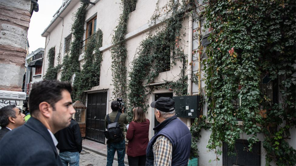 Journalists look at the apartment building from which James Le Mesurier fell to his death (11 November 2019)